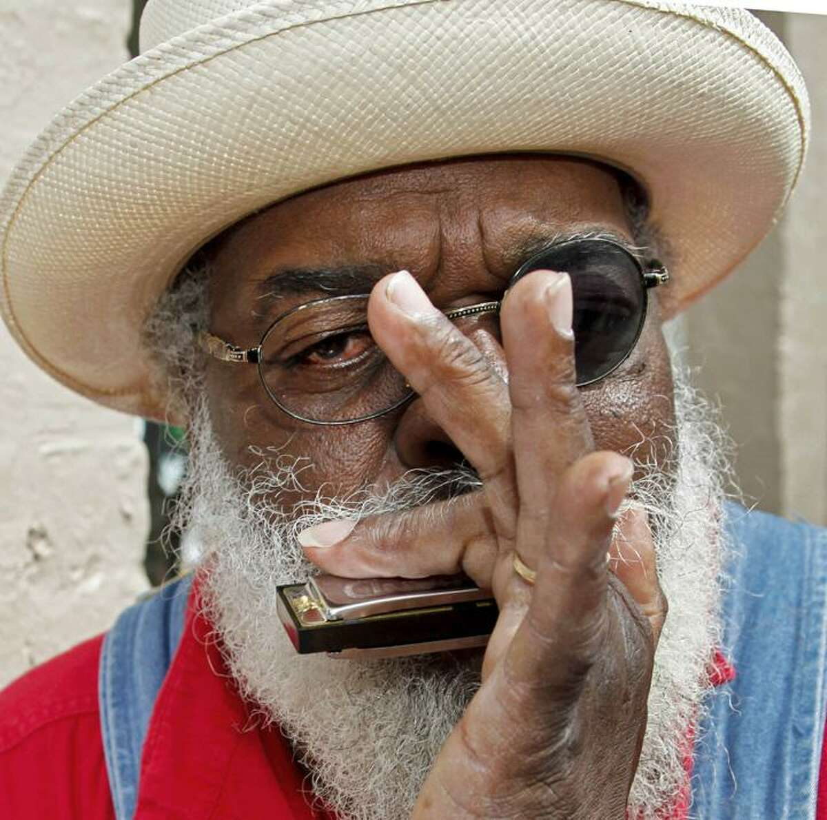 """In a Friday, April 2 photo, New Orleans street musician Elliott Small, aka """"Grandpa Elliott,"""" plays harmonica and sings in the French Quarter of New Orleans during an interview with an Associated Press reporter. Grandpa Elliott's popularity went global after the Playing for Change hit viral video """"Stand By Me"""" received millions of viewers. He will be a featured singer at the New Orleans Jazz and Heritage Festival that kicks off Friday. (AP)"""