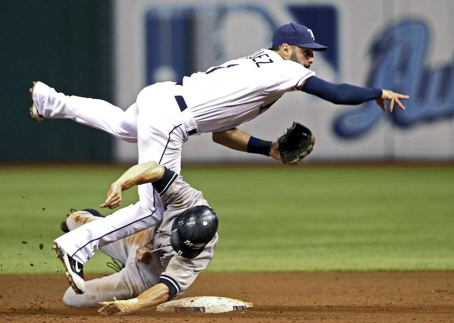 New York Yankees' Brett Gardner (11) slides in to disrupt a throw by Tampa Bay Rays second baseman Sean Rodriguez during the eighth inning of a baseball game Monday, July 18, 2011, in St. Petersburg, Fla. Eduardo Nunez was safe at first, and a run scored. (AP Photo/Mike Carlson) Photo: ASSOCIATED PRESS / AP2011