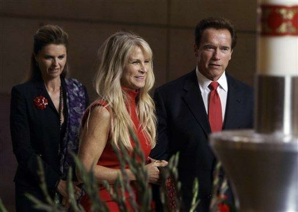 Dino De Laurentiis' widow Martha, center, is joined by California Gov. Arnold Schwarzenegger and his wife Maria Shriver at the funeral of Italian filmmaker Dino De Laurentiis, at the Cathedral of Our Lady of the Angels in Los Angeles Monday, Nov. 15, 2010. (AP Photo/Reed Saxon)