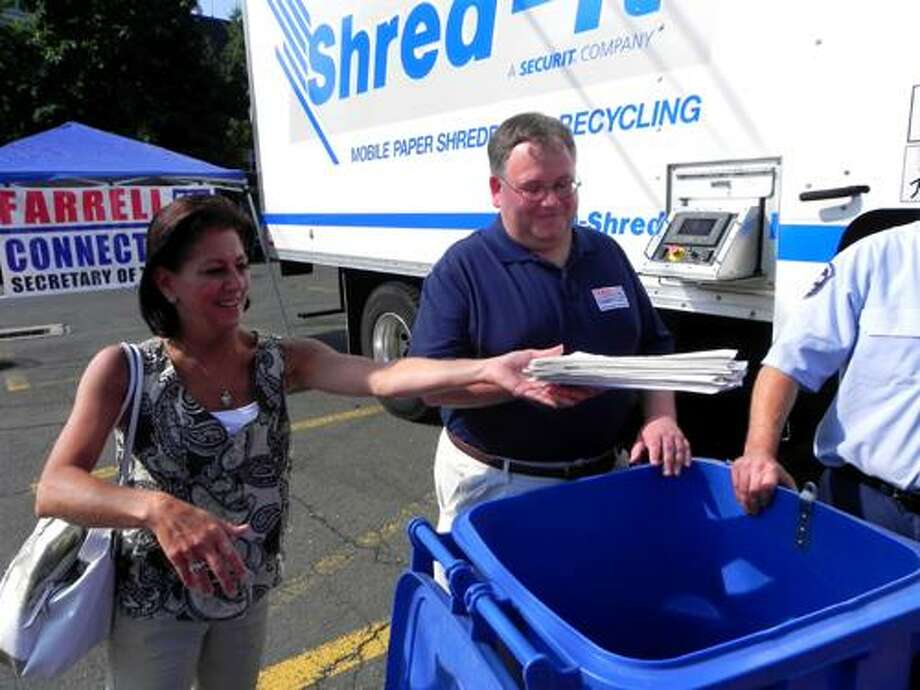 Photo Credit: Nancy Wuennemann Kathy Boucher of Cromwell shreds documents with Jerry Farrell Jr. in Middletown on Saturday.