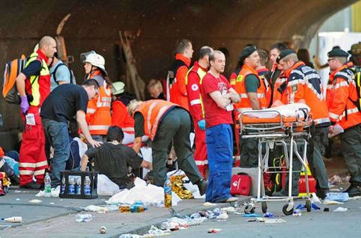 Firefighters and rescuers take care of a collapsed person after a stampede at this year's techno-music festival