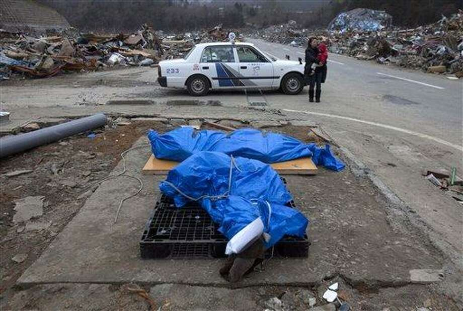 Behind two wrapped bodies lying on a roadside to be picked up by authorities, a woman holds her child next to a taxi she arrived in to check the damaged neighborhood of her family in the earthquake and tsunami destroyed town of Onagawa, Miyagi Prefecture, northeastern Japan Sunday, March 20, 2011. (AP Photo/David Guttenfelder) Photo: AP / AP