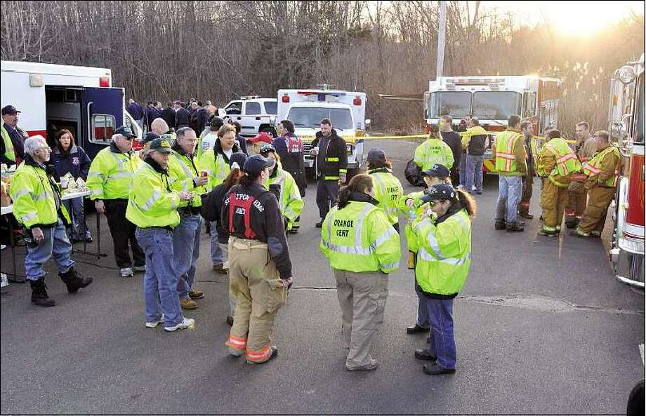 Memebers of the Orange Community Emergency Response Team gather with firefighters and police in the parking lot of Temple Emanuel of Greater New Haven to help search for the missing girl. Peter Casolino/Register.
