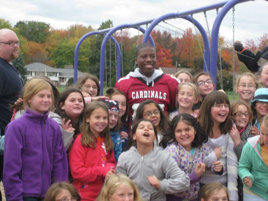 Woodside girls pose on the playground for a photo with wide receiver #87 Ernest Wingate. Jane Wiedenbeck