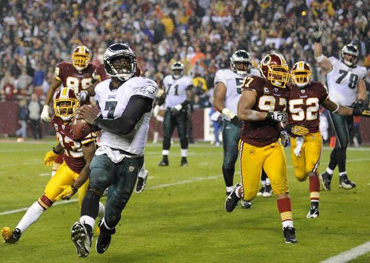Philadelphia Eagles quarterback Michael Vick rushes for a touchdown against the Washington Redskins during the first half of a NFL football game, Monday, in Landover, Md. (AP Photo/Nick Wass)