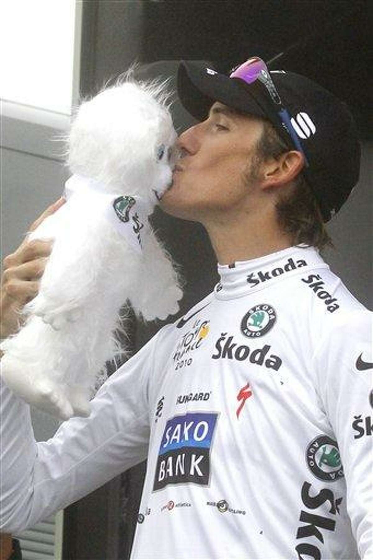 Stage winner Andy Schleck of Luxembourg, wearing the best young rider's white jersey, kisses the mascot on the podium after the 17th stage of the Tour de France cycling race over 174 kilometers (108.1 miles) with start in Pau and finish on Tourmalet pass, Pyrenees region, France, Thursday, July 22, 2010. (AP Photo/Laurent Rebours)
