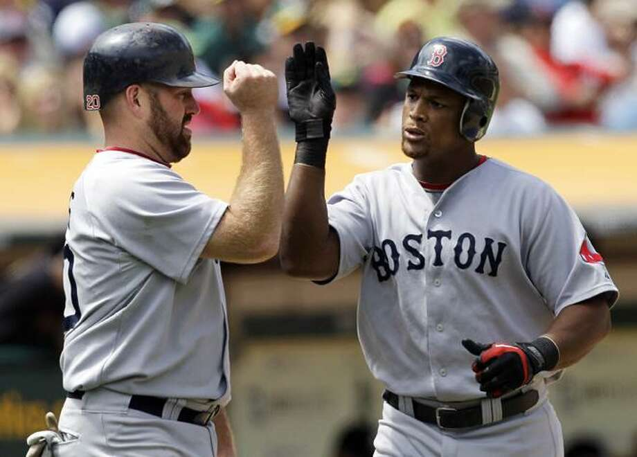 Boston Red Sox's Adrian Beltre, right, celebrates with teammate Kevin Youkilis after hitting a two-run home run that also scored Youkilis off a pitch from Oakland Athletics' Gio Gonzalez in the sixth inning of a baseball game in Oakland, Calif., Wednesday, July 21, 2010. (AP Photo/Jeff Chiu) Photo: AP / AP