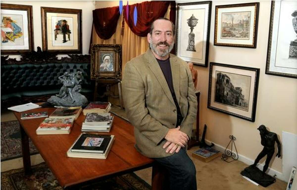 David Crespo, owner of the Brandon Gallery in Madison, with some of the art he sells including signed, limited edition Norman Rockwell prints behind him at left. Photo by Mara Lavitt/New Haven Register 11/13/10