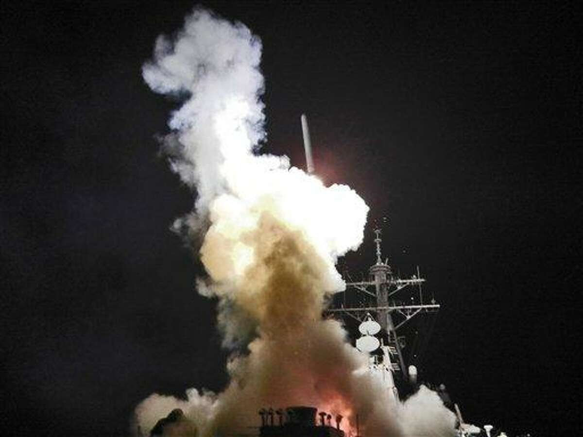 This Saturday, March 19, 2011 photo provided by the U.S. Navy shows the Arleigh Burke-class guided-missile destroyer USS Barry (DDG 52) as it launches a Tomahawk missile in support of Operation Odyssey Dawn from the Mediterranean Sea . The U.S. fired more than 100 cruise missiles from the sea while French fighter jets targeted Moammar Gadhafi's forces from the air on Saturday, launching the broadest international military effort since the Iraq war in support of an uprising that had seemed on the verge of defeat. (AP Photo/U.S. Navy, Fireman Roderick Eubanks)