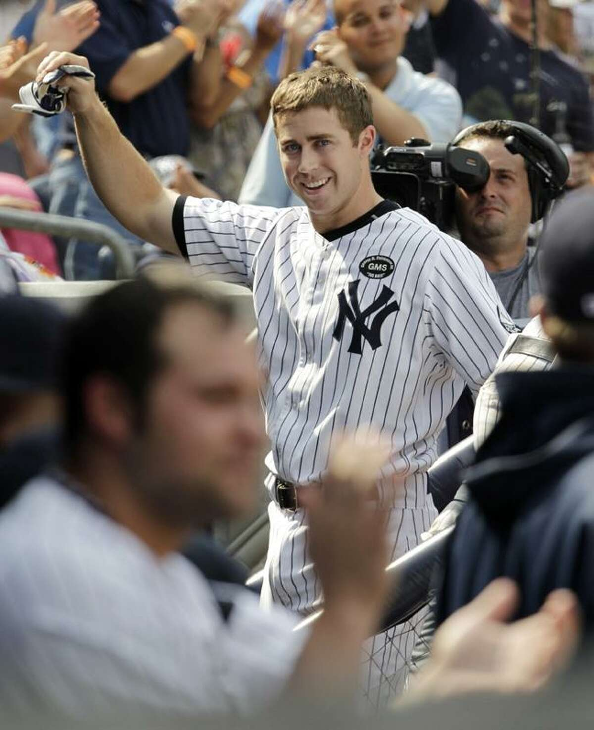 New York Yankees Colin Curtis (27) acknowledges the crowd with a curtain call after hitting a a three-run home run during the seventh inning of a baseball game against the Los Angeles Angels at Yankee Stadium on Wednesday in New York. The hit was Curtis' first career home run in the big leagues. (AP Photo/Kathy Willens)