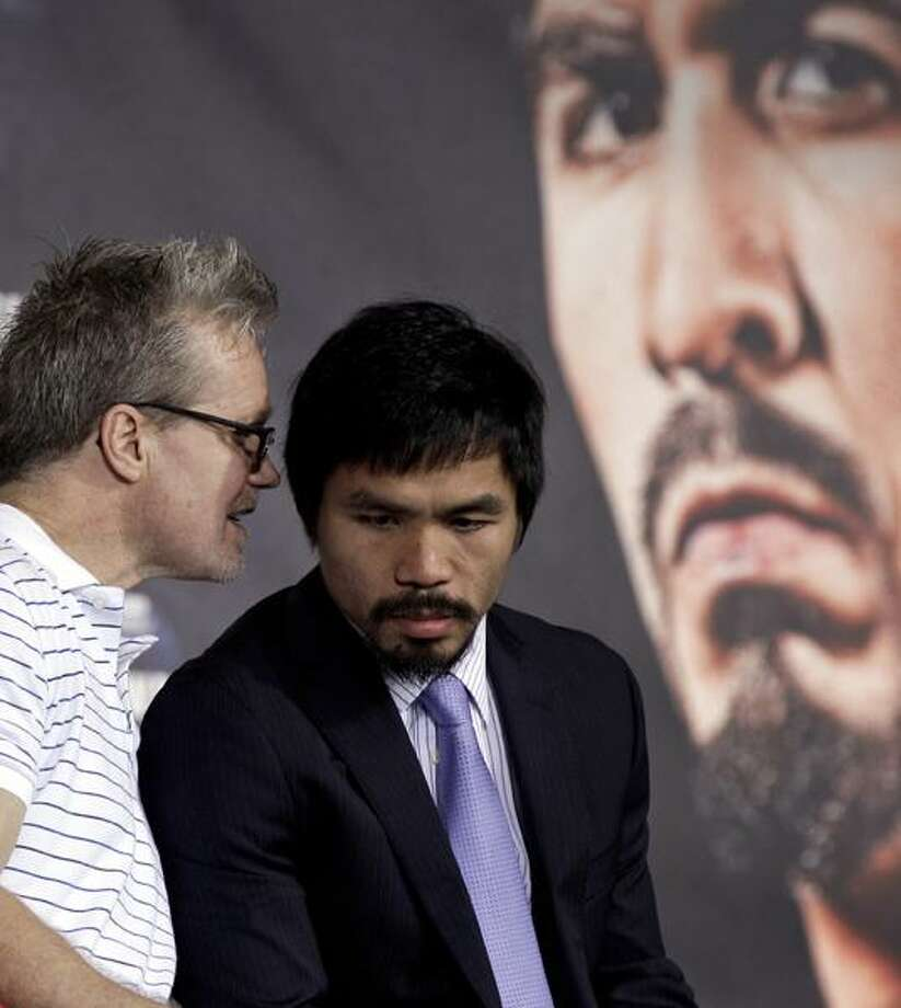 Manny Pacquiao, right, listens to his trainer Freddie Roach, left, during a news conference Wednesday in Arlington, Texas. Pacquiao is scheduled to fight Antonio Margarito Saturday night at Cowboys Stadium for the WBC World Super Welterweight title. (AP Photo/David J. Phillip) Photo: AP / AP