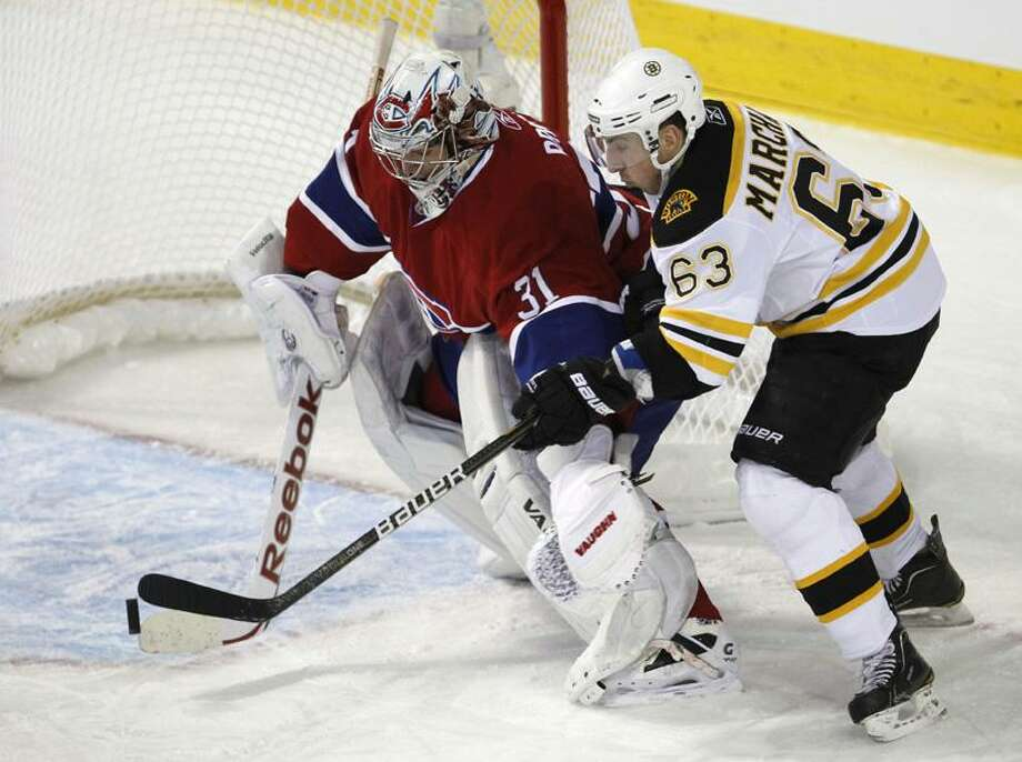 Montreal Canadiens goalie Carey Price blocks the puck away from Boston Bruins' Brad Marchand during the first period of an NHL hockey game Tuesday, March 8, 2011, in Montreal. (AP Photo/The Canadian Press, Paul Chiasson)
