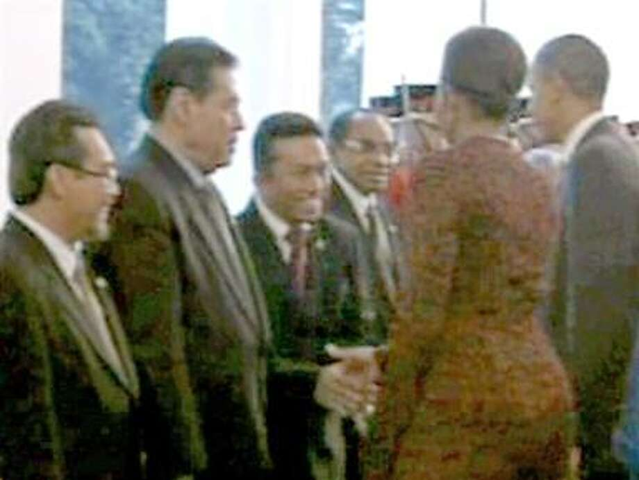 In this frame grab image made from video, first lady Michelle Obama shakes hands with Indonesian Information Minister Tifatul Sembiring, as the Obama's arrived in Jakarta on Tuesday, Nov. 9, 2010. Sembiring, who flaunts his conservatism, admits he shook hands with first lady Michelle Obama in welcoming her to Indonesia but says it wasn't his choice. (AP Photo/APTN) Photo: AP / APTN