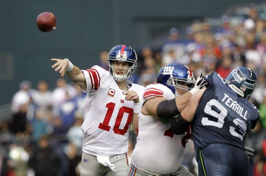 New York Giants quarterback Eli Manning (10) throws as Chris Snee holds back Seattle Seahawks' Craig Terrill in the first half of a NFL football game, Sunday, in Seattle. (AP Photo/Elaine Thompson) Photo: AP / AP