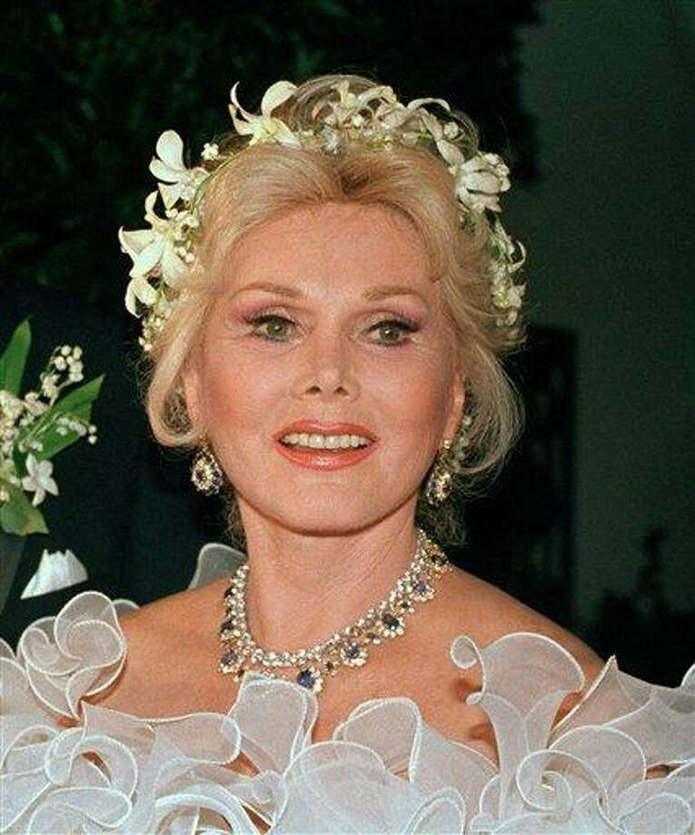 """FILE  - Actress Zsa Zsa Gabor is shown Los Angeles, in an Aug. 15, 1986 file photo. Zsa Zsa Gabor is scheduled to have surgery Tuesday, Sept. 17, 2007 for """"severe infection in her legs,"""" her publicist said. Gabor's publicist says the 93-year-old actress has been rushed to a hospital Saturday July 17, 2010 after falling out of bed and breaking several bones. The actress is partially paralyzed from a 2002 car accident, which forced her to use a wheelchair. She also reportedly had a stroke in 2005. (AP Photo/File) Photo: ASSOCIATED PRESS / AP"""