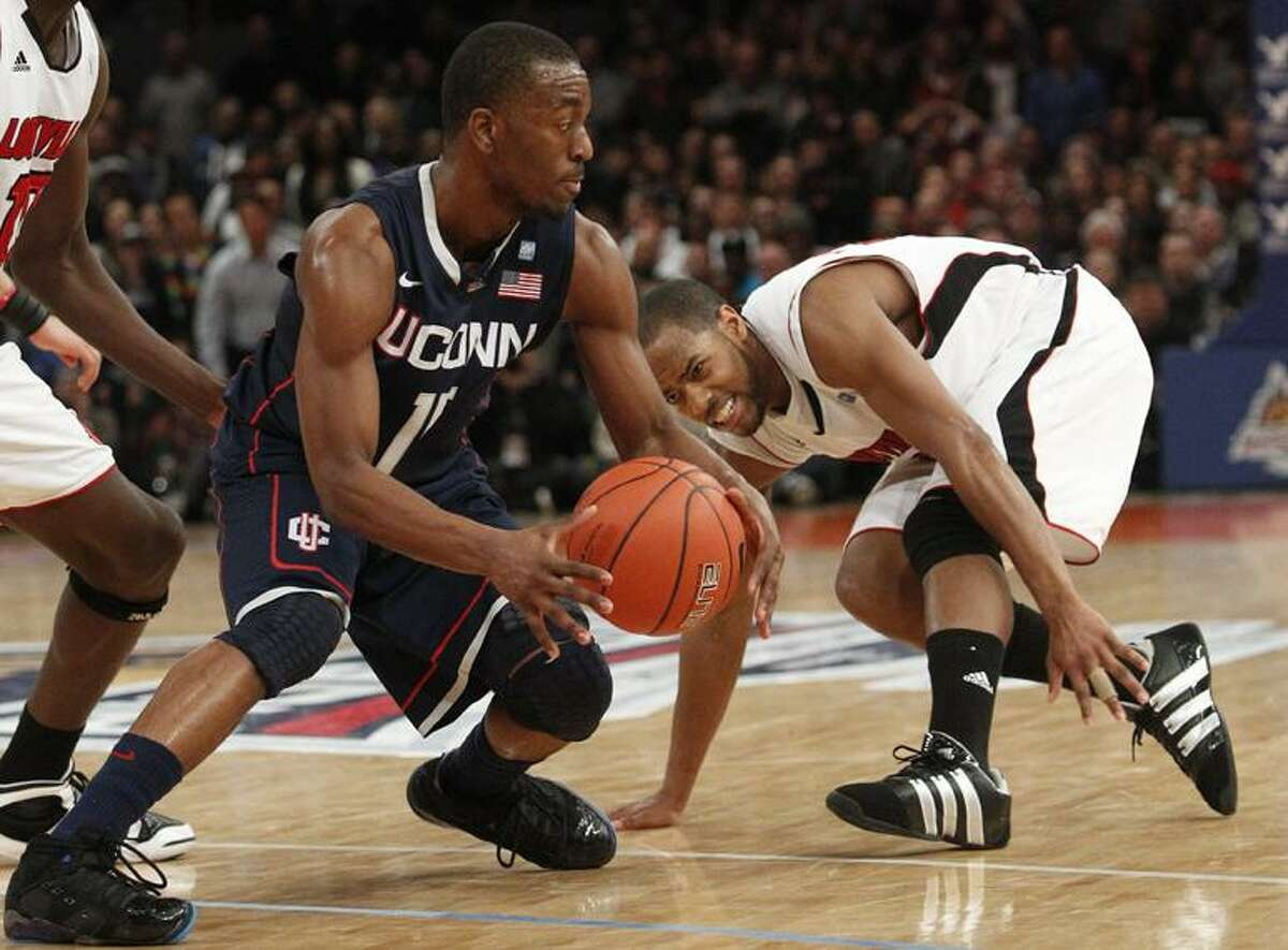 AP Connecticut's Kemba Walker (15) protects the ball from Louisville's Preston Knowles (2) during the second half of an NCAA college basketball game at the Big East Championship Saturday in New York. Connecticut won the game 69-66.