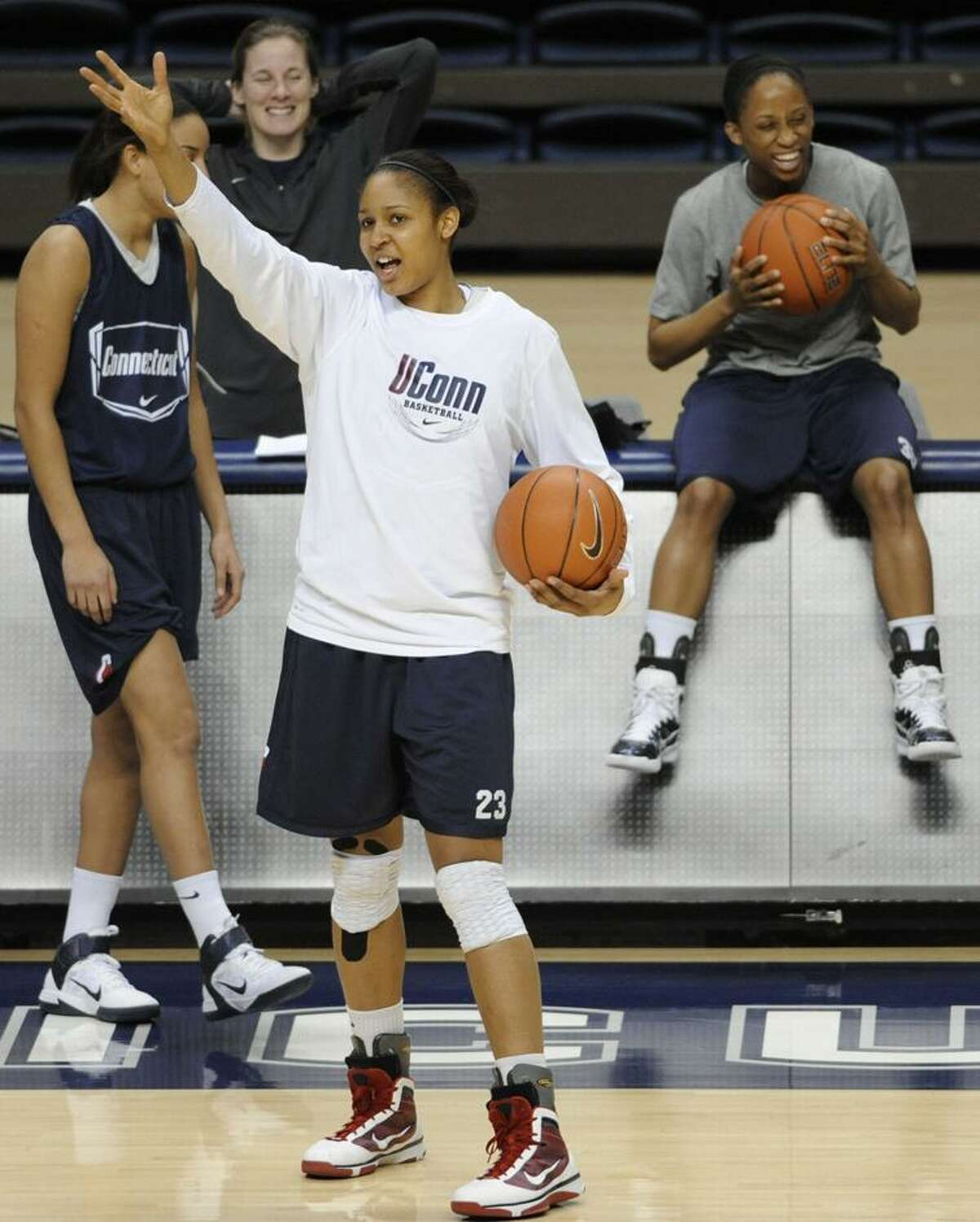 **HOLD FOR STORY BY DOUG FEINBERG** In this March 3, 2011 photo, Maya Moore, center, shares a light moment with teammate Lorin Dixon, right, during practice at the University of Connecticut in Storrs, Conn. (AP Photo/Jessica Hill)