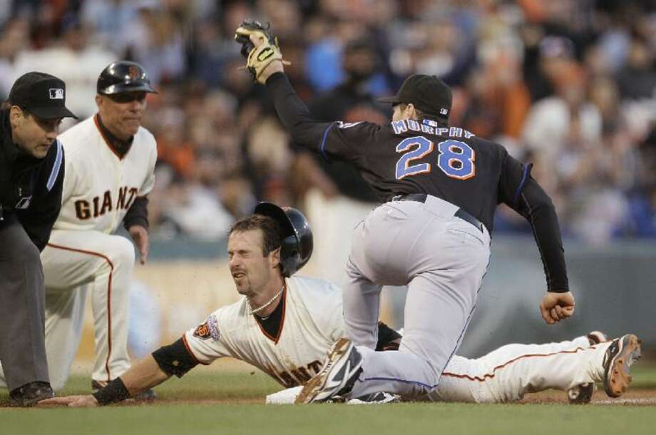 ASSOCIATED PRESS San Francisco's Aaron Rowand slides safely into third base as New York Mets third baseman Daniel Murphy, right, looks for the call during the seventh inning of their game in San Francisco Saturday. At left is third base umpire David Rackley and second from left is Giants third base coach Tim Flannery. Rowand was safe at third after the Giants' Miguel Tejada singled to right field.