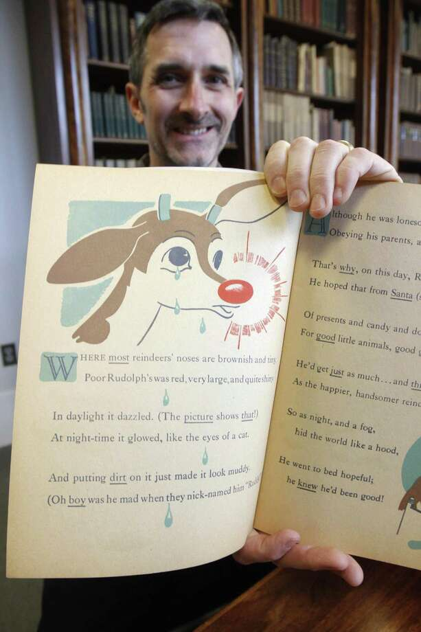 "Peter Carini holds a first edition of ""Rudolph, the Red-Nosed Reindeer"", part of a special collection at Dartmouth College, on Tuesday, Dec. 20, 2011 in Hanover, N.H. The book is from the estate of Robert May, a Dartmouth graduate who wrote the famous story in 1939 as part of a Montgomery Ward marketing campaign, and includes a list of other names he considered.(AP Photo/Toby Talbot) Photo: ASSOCIATED PRESS / AP2011"
