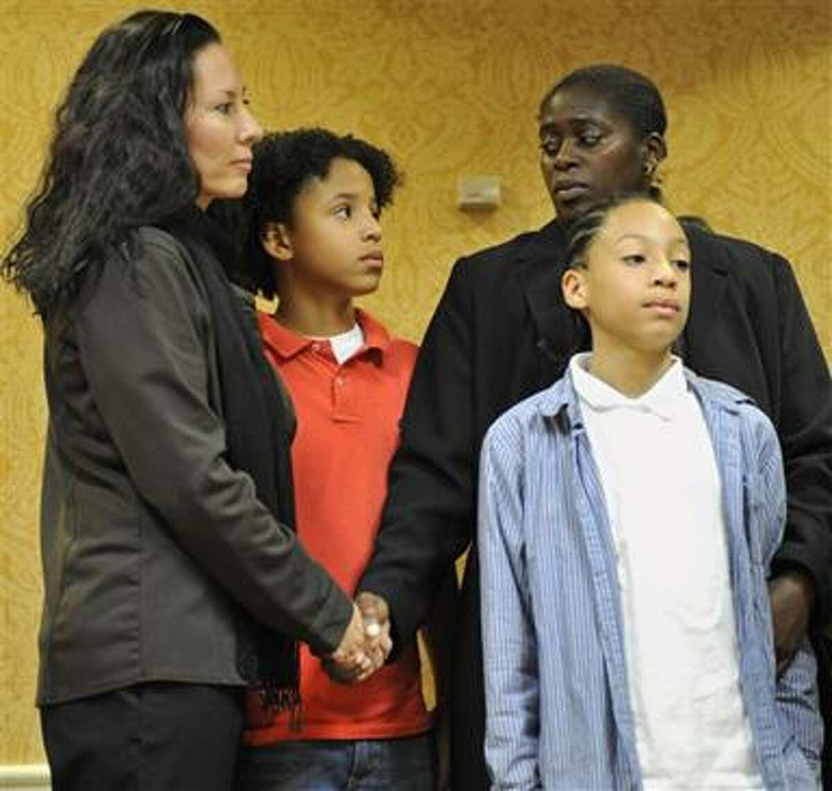 Suzanne Artis, left, and her spouse, Geraldine, second from right, stand with their children Gezani, second from left, and Zanagee, right, during a news conference for the Gay & Lesbian Advocates & Defenders, or GLAD, center, to discuss the filing of a federal lawsuit, in Hartford, Conn., Tuesday, Nov. 9, 2010. Two new lawsuits have been filed on behalf of gay and lesbian couples in four states to challenge a 1996 law denying married gay couples federal benefits. The lawsuits were filed Tuesday in federal courts in Connecticut and New York. They were filed on behalf of couples in Connecticut, Vermont, New Hampshire and New York. (AP Photo/Jessica Hill)