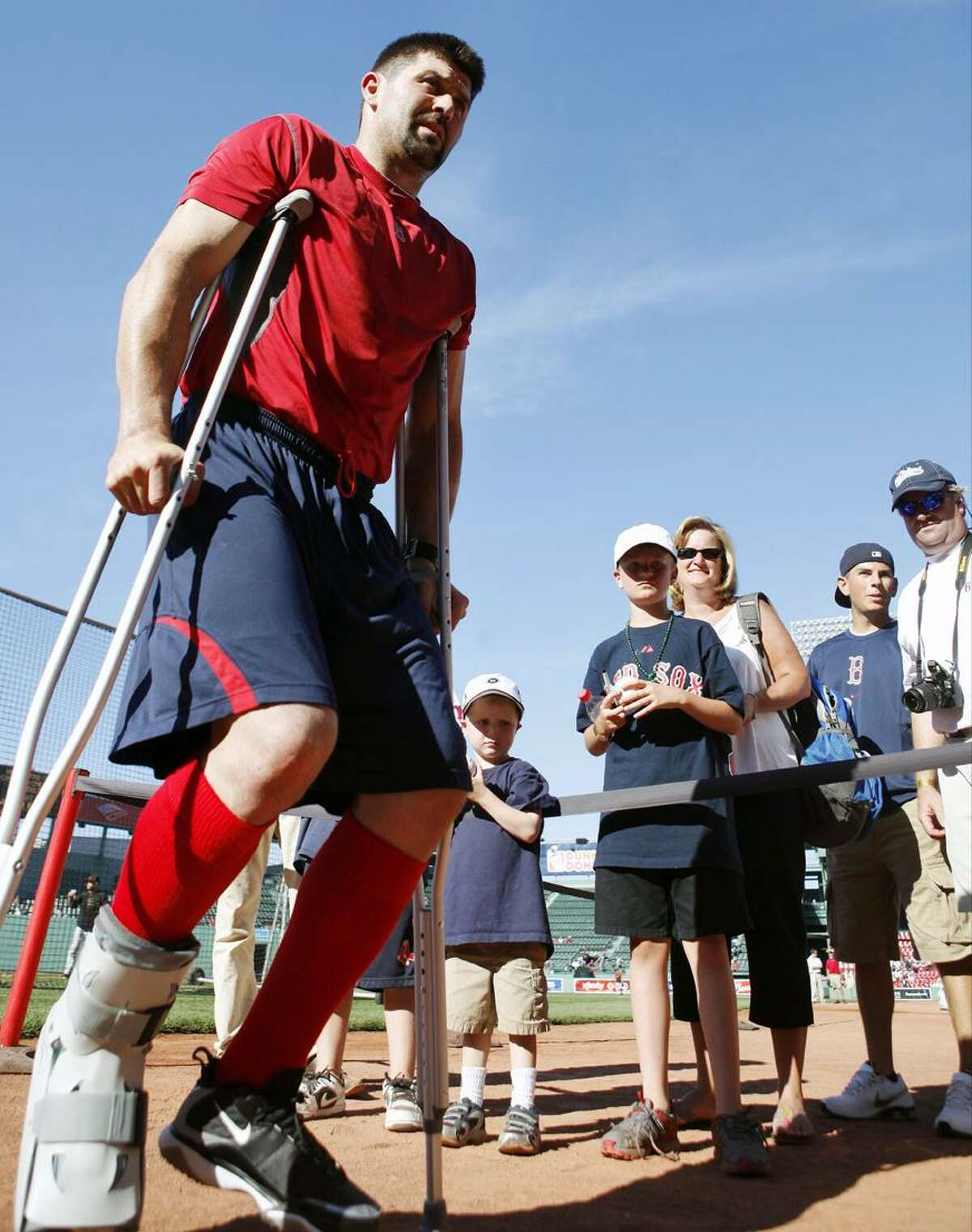This July 3 file photo shows Boston Red Sox's Jason Varitek leaving the field on crutches after batting practice before a baseball game between the Red Sox and the Baltimore Orioles in Boston. The floor of the Red Sox clubhouse was filled with black equipment bags as players packed for their 10-day West Coast trip. Amid the clutter, the stuff that revealed the team's current condition was still hard to miss. The protective boot on Dustin Pedroia's broken left foot. The splint on Victor Martinez's fractured left thumb. The crutches leaning against Varitek's locker, and the boot on his broken right foot. (AP Photo/Michael Dwyer,File)