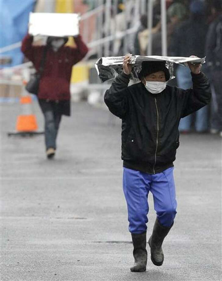 A man carries a heat blanket as he leaves a radiation emergency scanning centre in Koriyama, Fukushima Prefecture, Japan, Tuesday, March 15, 2011 four days after a giant quake and tsunami struck the country's northeastern coast. (AP Photo/Mark Baker) Photo: ASSOCIATED PRESS / AP2011
