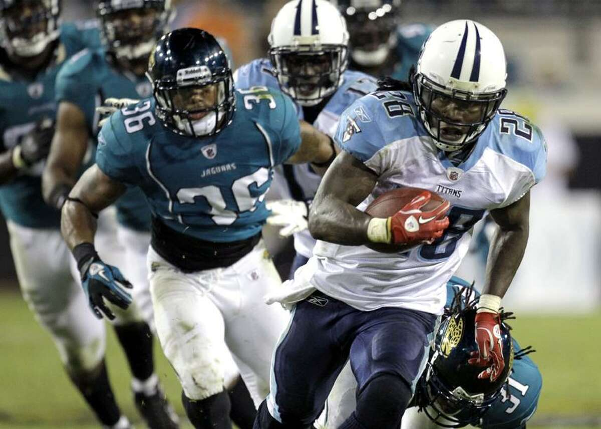 Tennessee Titans running back Chris Johnson (28) runs for a 35-yard touchdown past Jacksonville Jaguars safety Courtney Greene (36) during the second half of a NFL football game in Jacksonville, Fla., Monday, Oct. 18, 2010. Tennessee won 30-3. (AP Photo/John Raoux)