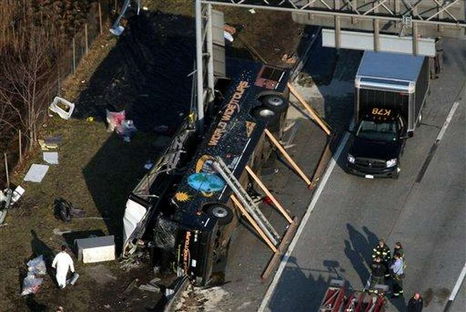 Emergency personnel respond to the bus crash on Interstate 95 in the Bronx borough of New York, Saturday, March 12, 2011. At least 14 people died when the bus, returning to New York from a casino in Connecticut, flipped onto its side and was sliced in half by the support pole for a large sign.(AP Photo/The Journal News, Frank Becerra Jr.) NYC METRO OUT; TV OUT; MAGS OUT; NO SALES; TV OUT; MANDATORY CREDIT: THE JOURNAL NEWS, FRANK BECERRA, JR. Photo: AP / The Journal News