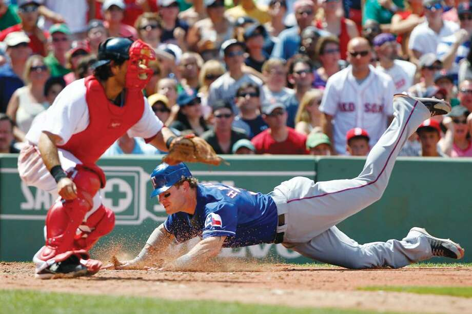 Texas Rangers' Josh Hamilton, right, scores on a double by Nelson Cruz as Boston Red Sox catcher Dusty Brown waits for the throw in the fourth inning of a baseball game, Sunday, in Boston. (AP Photo/Michael Dwyer) Photo: AP / AP