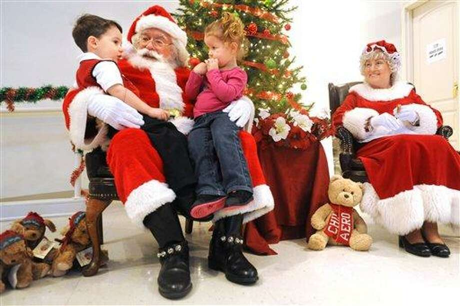 Three-year-old cousins Luke Luttrell, left, and Jaylin Kundert, visit  Santa and Mrs. Claus during a recent employee Christmas party at Wendell Foster's Campus for Developmental Disabilities in Owensboro, Ky.  Associated Press Photo: AP / Messenger-Inquirer