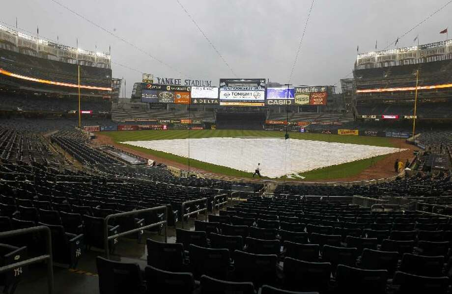 ASSOCIATED PRESS The field is covered at Yankee Stadium for the game between the New York Yankees and the Tampa Bay Rays, Friday in New York. The game was called due to rain, delaying Derek Jeter's chase for 3,000 hits. He has 2,998.