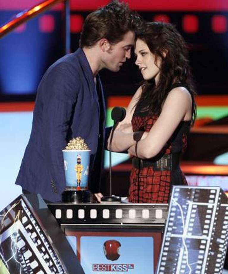 "In this May 31, 2009, file photo, Robert Pattinson, left, and Kristen Stewart accept the award for best kiss for ""Twilight"" at the MTV Movie Awards in Universal City, Calif. (AP) Photo: AP / AP2009"