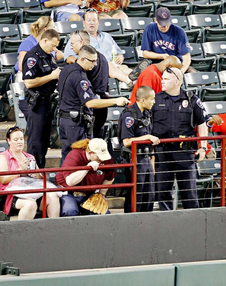 AP PHOTO/THE DALLAS MORNING NEWS/G.J. McCARTHY Arlington Police Department officers gather near where a Texas Rangers fan fell about 20 feet onto concrete reaching out for a baseball tossed his way by All-Star outfielder Josh Hamilton during a game between the Rangers and Oakland Athletics, Thursday night in Arlington, Tx. Shannon Stone, a 39-year-old firefighter from Brownwood, died at a hospital Thursday night, the Tarrant County Medical Examiner's Office said.