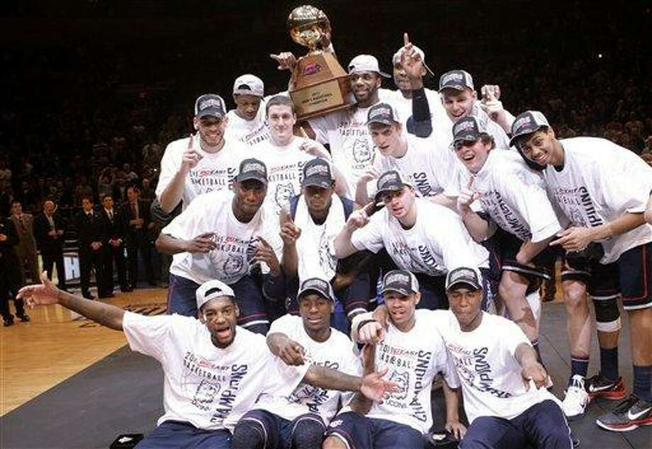Connecticut celebrates while holding the tournament trophy after an NCAA college basketball game against Louisville at the Big East championship, Saturday, March 12, 2011, in New York. Connecticut won 69-66. (AP Photo/Frank Franklin II) Photo: AP / AP