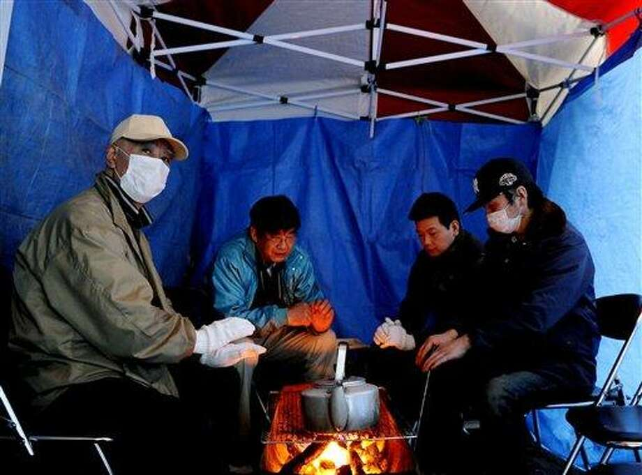 Evacuees warm themselves in a tent set up at a shelter in Rikuzentaketa, Iwate prefecture, Japan, Saturday, March 12, 2011, a day after one of Japan's strongest earthquakes ever recorded hit the country's east coast. (AP Photo/Kyodo News) Photo: AP / Kyodo News