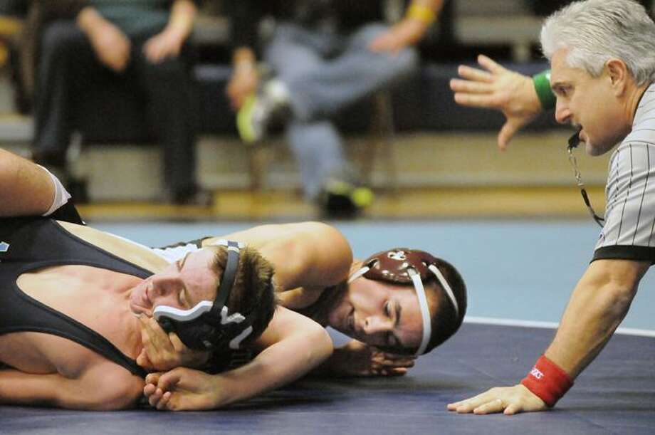 The Middletown Press 12.21.11  Middletown's Johhny Carrero wins his match against Bristol Central's Zach Mastromarino in the 126-pound weight class. Bristol Central defeated the Blue Dragons 53-24 Wednesday night at the LaBella-Sullivan Gymnasium at MHS. / TheMiddletownPress