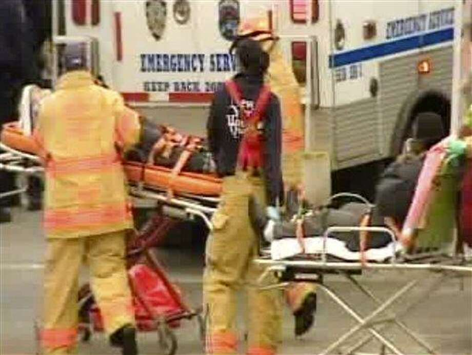 In this image taken from video released by WABC-TV 7 in New York, emergency personnel load two of the victims of a bus crash on Interstate 95 in the Bronx borough of New York, Saturday, March 12, 2011. At least 14 people died when the bus, returning to New York from a casino in Connecticut, flipped onto its side and was sliced in half by the support pole for a large sign. (AP Photo/WABC-TV 7) NO SALES Photo: AP / WABC-TV 7