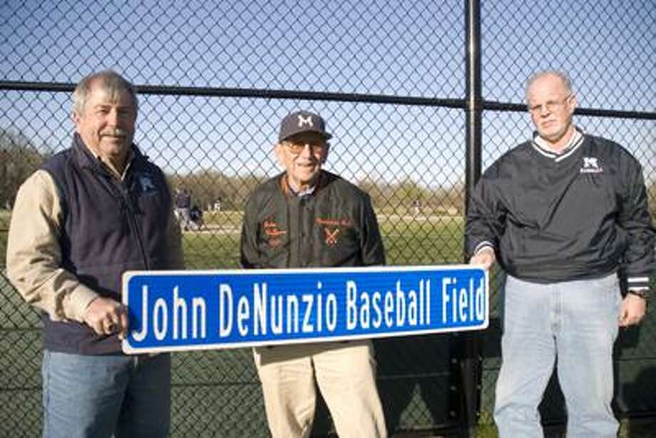 Mike Pitruzzello, MHS director of athletics (left), former Middletown High baseball coach John DeNunzio (center) and former Middletown High baseball coach, John Geary (right), hold up a sign behind the new John DeNunzio baseball field at Middletown High Monday after DeNunzio threw out the ceremonial first pitch. (Max Steinmetz / Special to the Press)
