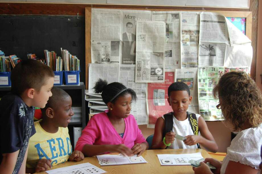 John Sanchez-Menard, Justin Walker, India Weston and Kenny Fountain, all rising fourth-graders at Macdonough School, work on a math lesson with teacher Joanne Jukins. Jukins and all her fellow teachers at Macdonough are volunteering their time to teach summer school, after the district cut the annual program to save money.
