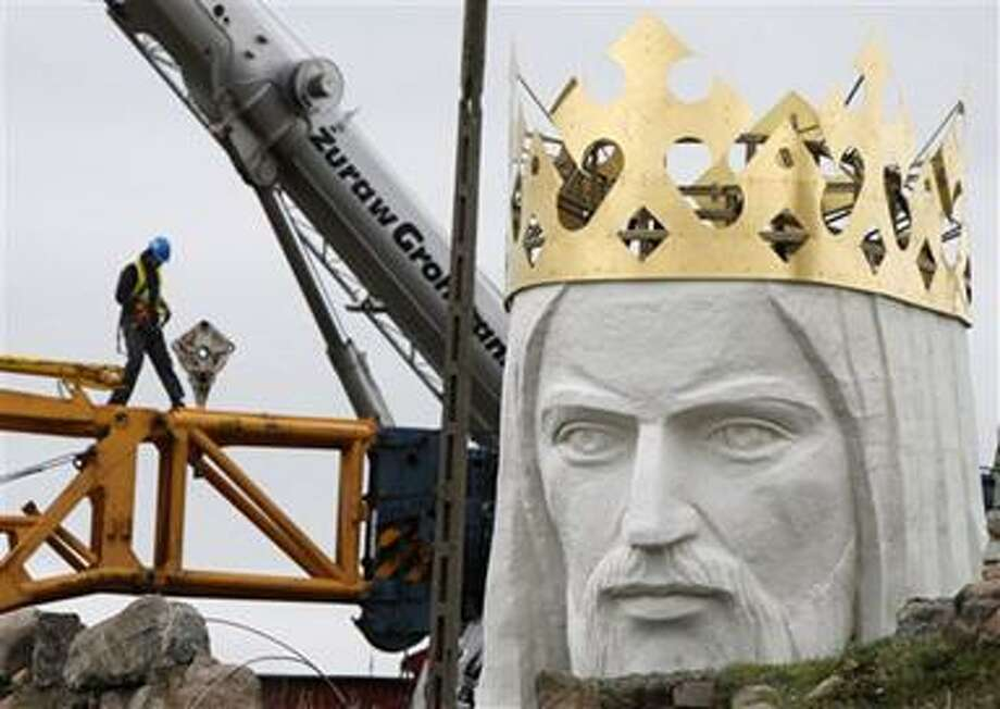 Workers struggling against wind to assemble a crane that is to lift 32-ton head and shoulders to top a giant concrete and metal statue of Jesus in Swiebodzin, western Poland, Friday, Nov.5, 2010. The 108 feet (33 meters) statue is to be the world's tallest and is supposed to attract pilgrims and boost business in the town. (AP Photo/Czarek Sokolowski) Photo: AP / AP
