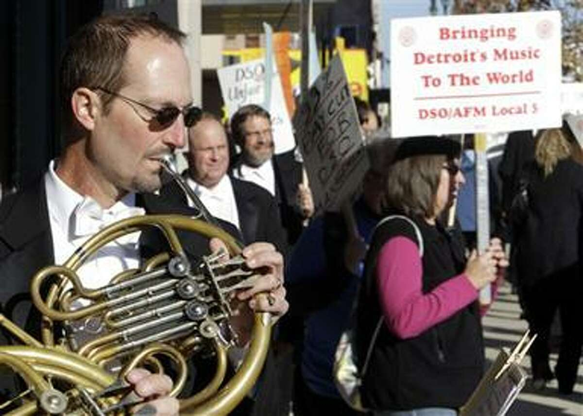 FILE - Detroit Symphony Orchestra member Karl Pituch plays his French horn as he serenades fellow members walking a picket line outside the Max M. Fisher Music Center in Detroit, in this Oct. 4, 2010 file photo. The Detroit Symphony Orchestra said in a statement Wednesday Oct. 13, 2010 it has canceled all concerts through Nov. 7, citing a strike by musicians protesting sharp cuts in pay. (AP Photo/Paul Sancya, File)