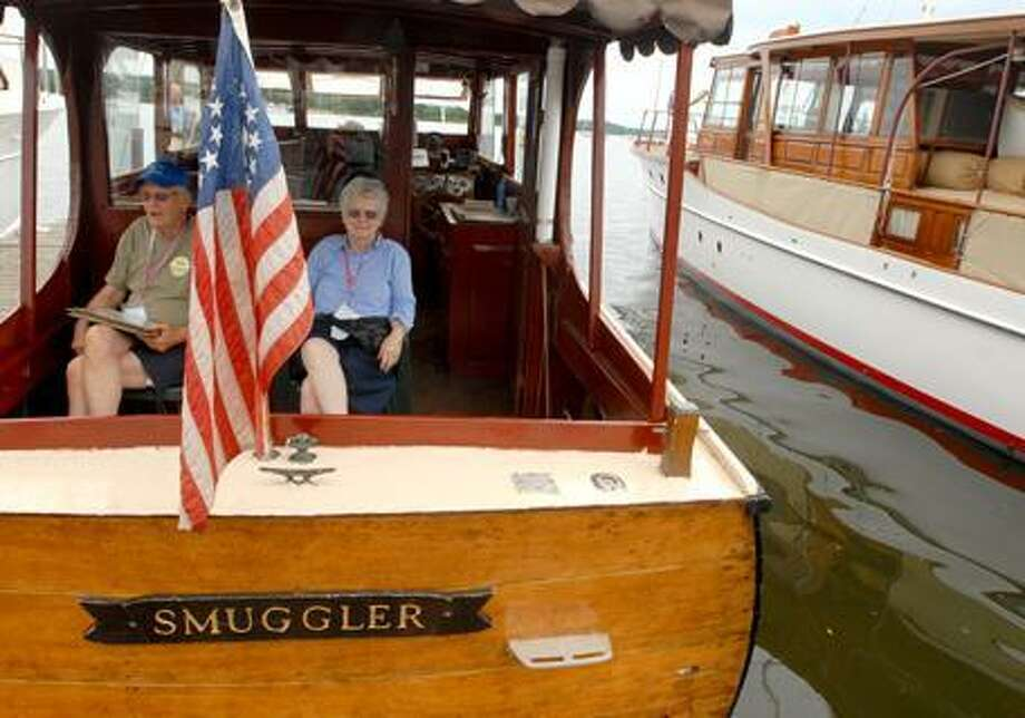 Bob and Bev VanSteenbergen (CQ) of Guilford show off their 1959 custom made 30-foot cabin cruiser designed by Ken Smith exhibited during the Mahogany Memories boat show in Essex. (PETER HVIZDAK)