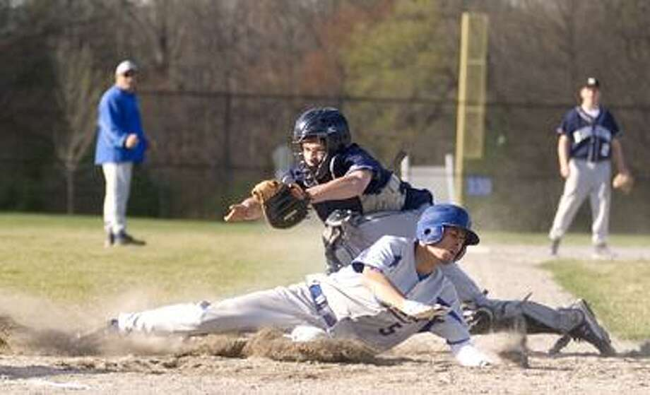 Middletown's Vinny Quintiliano is late to apply the tag as a Newington runner crosses the plate. Middletown lost its first-ever game at the new John DeNunzio Baseball Field Monday, a 6-3 defeat. (Max Steinmetz / Special to the Press)