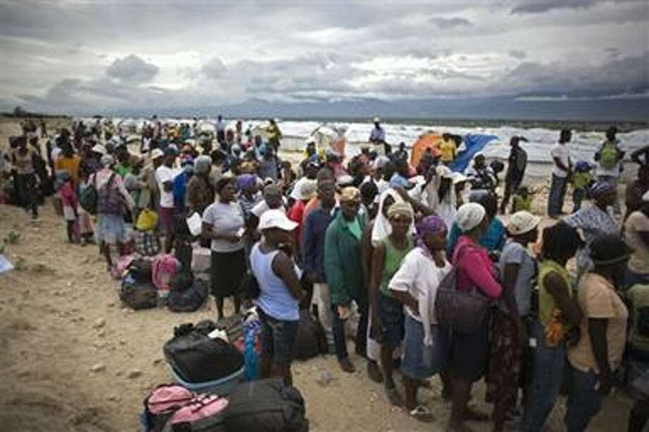 People wait in line to be evacuated  from the Corail-Cesselesse tent refugee camp before the arrival of tropical storm Tomas in Port-au-Prince, Haiti, Thursday, Nov. 4, 2010. Fear and confusion set in among more than 1 million Haitians advised to leave earthquake homeless camps in the country's capital.(AP Photo/Ariana Cubillos) Photo: AP / AP