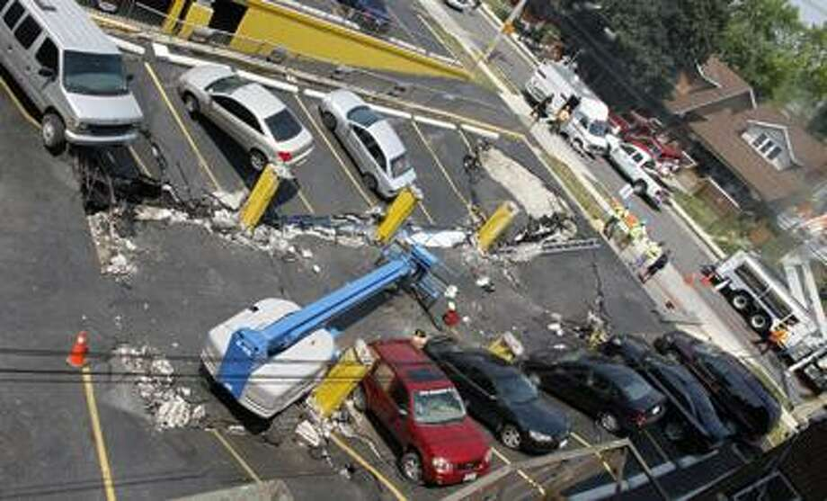 A parking garage was rendered into rubble Thursday, July 8, 2010 when the two-story structure collapsed, sending one man to the hospital and crushing several vehicles below, Windsor, Ont., Canada.  Emergency response teams entered the debris to help search for any trapped victims. (AP Photo/The Canadian Press, Greg Plante) Photo: AP / The Canadian Press