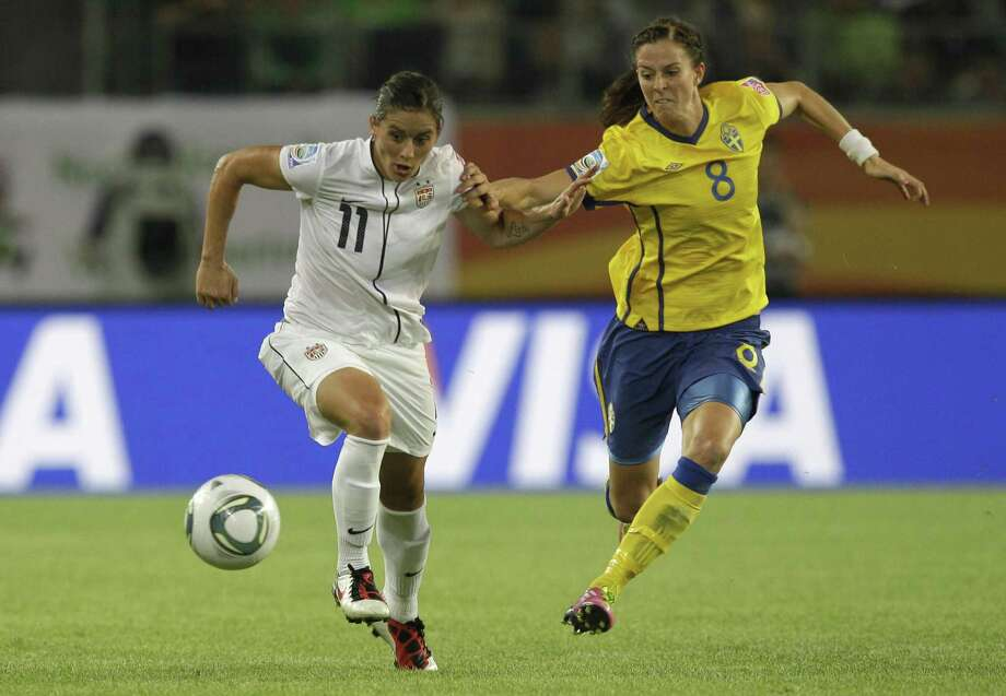 United States' Alex Krieger and United States' Amy Rodriguez challenge for the ball during the group C match between Sweden and the United States at the Women's Soccer World Cup in Wolfsburg, Germany, Wednesday, July 6, 2011. (AP Photo/Marcio Jose Sanchez) Photo: ASSOCIATED PRESS / AP2011