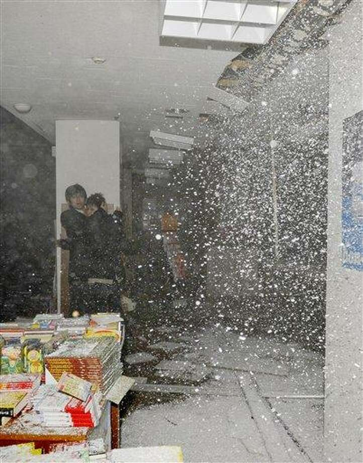 People at a book store react as the store's ceiling falls in Sendai, northern Japan Friday, March 11, 2011. Japan was struck by a magnitude-8.8 earthquake off its northeastern coast Friday, triggering a 13-foot (4-meter) tsunami that washed away cars and tore away buildings along the coast near the epicenter. Photo: AP / Kyodo News