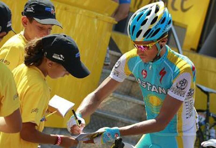 Alberto Contador of Spain signs autographs prior to the start of the 12th stage of the Tour de France cycling race over 210.5 kilometers (130.8 miles) with start in Bourg-de-Peage, and finish in Mende, France, Friday. Photo: AP / AP