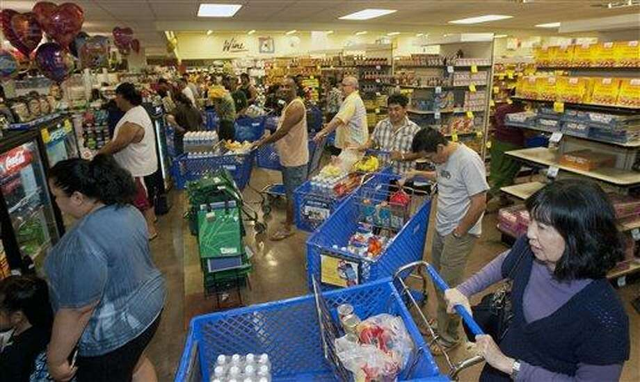 Hundreds of Oahu residents flocked to the Times Supermarket to purchase water and supplies Thursday, March 10, 2011 in Honolulu. The state of Hawaii is under a tsunami warning due to a large 8.9 earthquake off Japan. The earthquake is believed to have generated a tsumani wave. The Pacific Tsunami Center expects the wave to hit Hawaii at 2:59 a.m. Hawaiian Standard Time. (AP Photo/Eugene Tanner) Photo: ASSOCIATED PRESS / AP2011