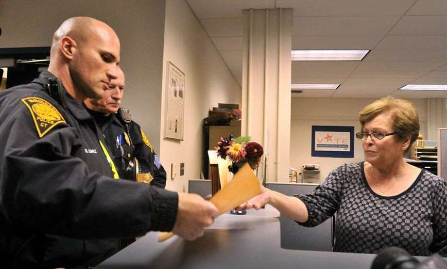 Bridgeport  officer R. Lopez (L) turns over an envelope containing the official voting returns from Bridgeport to Yolanda Santiago.  Santiago is a processing technician for the Stcretary of State.   Melanie Stengel/Register      11/5/10